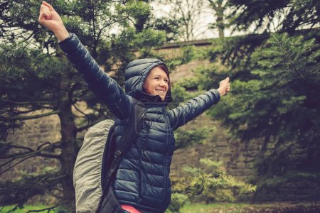 Smiling Student woman with raised hands hiking in forest