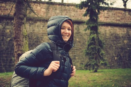 Student woman hiking in forest. Female hiker smiling happy portrait on rainy day during a trekking trip
