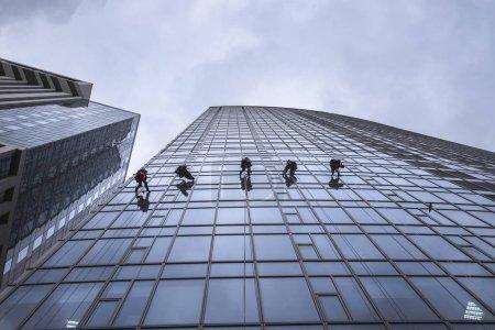 Photo pour Laveuses de fenêtres nettoyant la façade vitrée d'un gratte-ciel, travaux à haut risque. Tour Gulliver à Kiev, Ukraine - image libre de droit