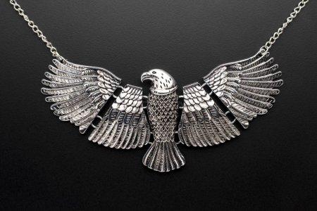 Foto de Águila de collar de plata en una cadena aislada en negro - Imagen libre de derechos