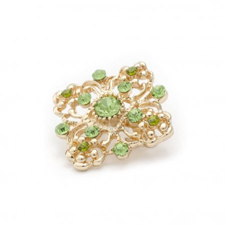 gold brooch with emeralds isolated on white