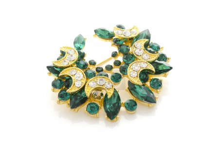 golden brooch with emeralds and diamonds isolated on white