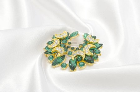 golden brooch with emeralds and diamonds on silk