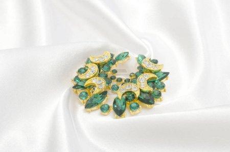 broche dorée d'émeraudes et de diamants sur soie