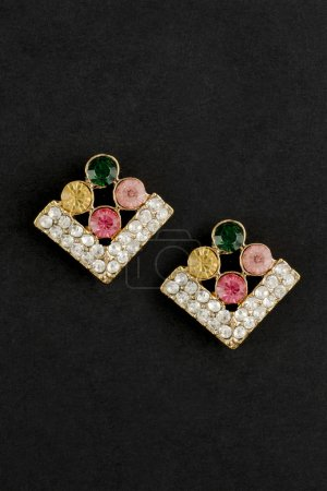 gold rhombuses earrings with gem stones isolated on black
