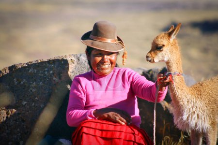 Woman in traditional clothes with lama sitting on stone in Puno