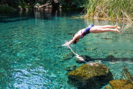 Photo pour Young woman in blue swimsuit diving in the blue water river. - image libre de droit