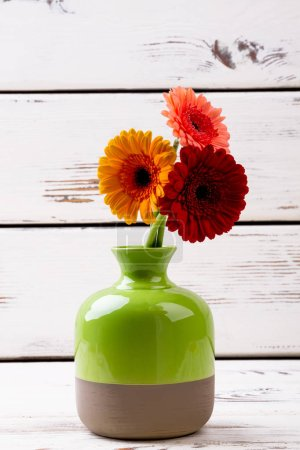 Enameled vase with gerberas.