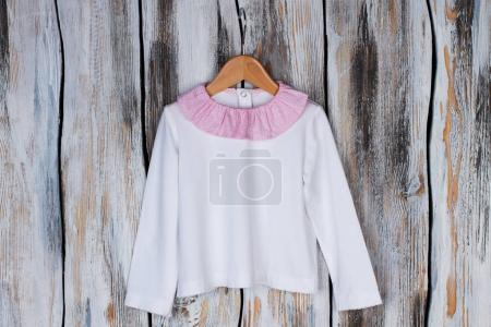 Photo for White top with pink collar rustic wooden background. Soft fabric and cute girlish details. Girls clothing collection. - Royalty Free Image