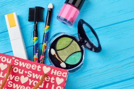 Foto de Cosmética de diseño de moda, fondo de color. Conjunto plano de bolsa de compras roja abierta con cosméticos sobre fondo de madera azul . - Imagen libre de derechos
