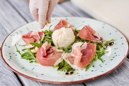Photo for Chef cooking delicatessen salad at restaurant. Chef hand putting cashew nuts in prosciutto and arugula salad with burratto. Appetizing restaurant dish. - Royalty Free Image