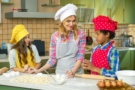 Photo for Young woman and children cooking. People making pastry. Special biscuits recipes. - Royalty Free Image