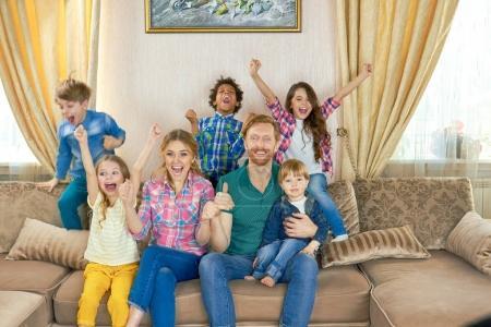 Photo pour Joyeux famille regardant la télé. Des gens joyeux sur le canapé. chaînes de télévision les plus populaires . - image libre de droit