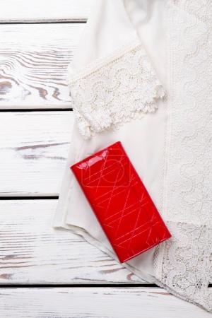 Photo pour Chemisier de dentelle blanche et rouge portefeuille, bouchent. Vertical recadrée vue. Fond de surface de bureaux en bois. - image libre de droit