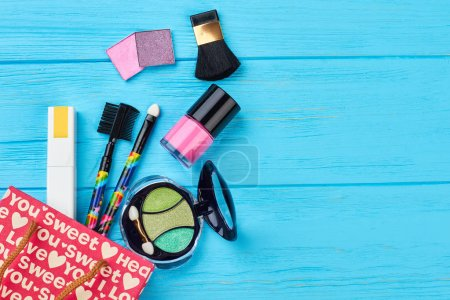 Photo for Shopping bag and cosmetics, wooden background. Cosmetics come out from red gift bag. Make up products and copy space. - Royalty Free Image