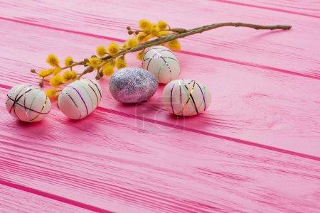 Photo pour Oeufs de Pâques décorés et saule chatte. Oeufs en polystyrène moderne pour les vacances de Pâques sur bois rose avec espace de copie. Décoration festive de printemps . - image libre de droit