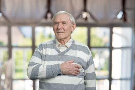 Photo for Very old man with sudden heart attack. Senior touching his chest in windows background. - Royalty Free Image