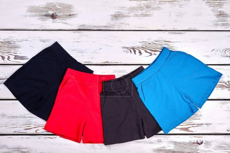 Photo for Set of kids colored cotton shorts. Collection of new brand shorts for childrens on white wooden background. Kids summer fashion style. - Royalty Free Image