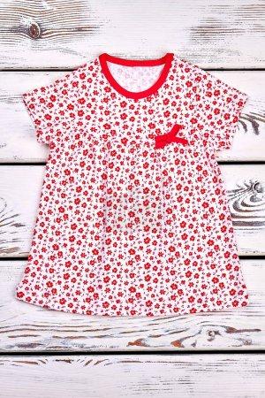 Photo pour Infat bébé blanc à motifs robe de soleil. Bébé fille casual robe blanche avec un motif de petites fleurs rouges, vieux fond en bois . - image libre de droit