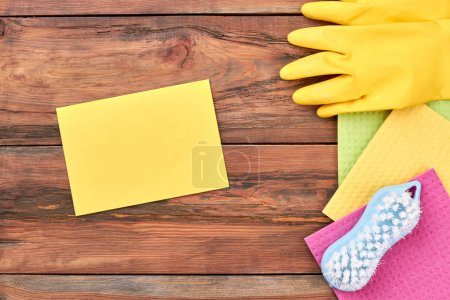 Photo for Set of equipment for home cleaning. Empty paper card and equipment for cleaning on wooden background. Supplies for house cleaning. - Royalty Free Image