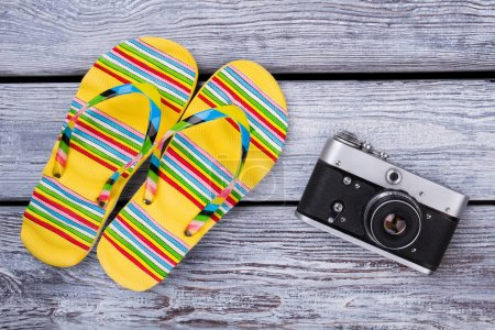 Photo for Travel and vacation items on wooden table. Flip floppers and photo camera. Top view with copy space. - Royalty Free Image