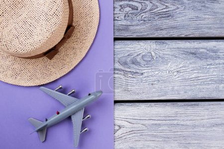Photo for Straw hat and toy airplane. Wooden and purple background. Travel and resort concept. - Royalty Free Image