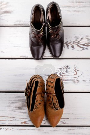 Photo for Two pairs of female ankle boots. Women stylish autumn shoes on white wooden background. Feminine fashion and style. - Royalty Free Image