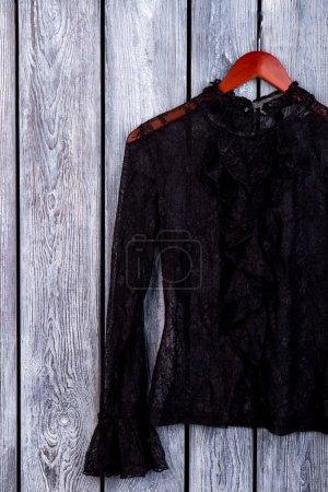 Photo pour Chemisier féminin en dentelle élégante sur cintre. Femmes beaux vêtements sur un vieux fond en bois. Mode féminine et élégance . - image libre de droit