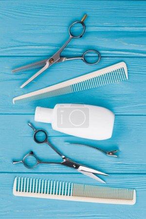 Photo pour Peignes, ciseaux et shampooing sur fond bois. Soins capillaires masculins sur fond bleu. Couché plat, vue du dessus . - image libre de droit
