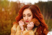 Attractive young woman with red hair. Closeup winter portrait. Curly hairstyle and makeup