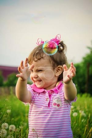 The child blows bubbles. Selective focus.