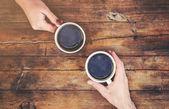 """Постер, картина, фотообои """"Чашки с кофе в руках мужчин и женщин. Выборочный фокус."""""""