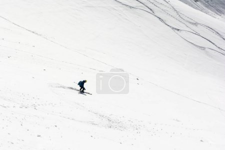 Skier during the downhill ride in the mountains.