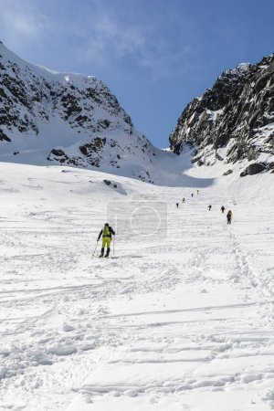 Spring ski touring and hiker approach on the mountain pass (Zawrat) in the Tatra Mountains.