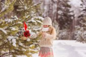 Beautiful cute girl with a winter forest decorating a Christmas tree with a gift. On the tree there is a basket with flowers and a toy. New Year concept.