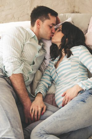 happy family of pregnant woman and young husband are kissing