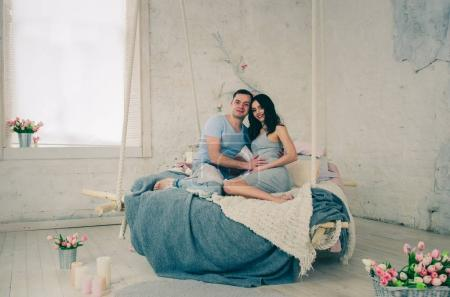 happy family of pregnant woman and young husband sitting on bed