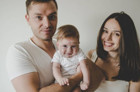 young family holding little baby in hands smiling
