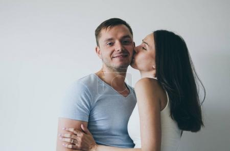 beautiful young couple kissing and smiling on white background