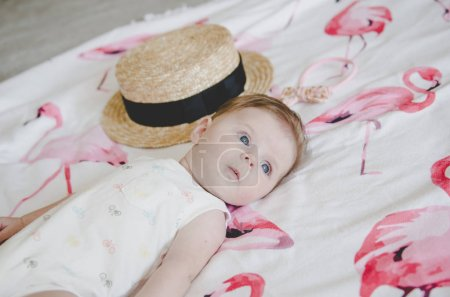 Beautiful little baby girl in white body suit looking on camera