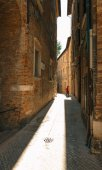 Urbino, Italy - August 9, 2017: A small street in the old town of Urbino. sunny day.