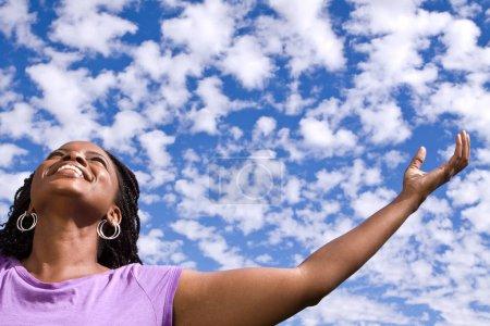 Photo pour Femme à bras ouverts avec des nuages dans le background.p - image libre de droit