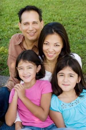 Loving Asain parents and their daughters smiling.