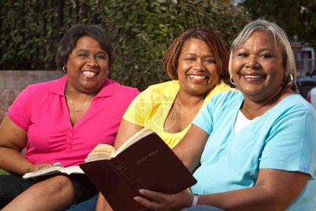 Photo pour Petit groupe de femmes de parler et de lire la Bible. - image libre de droit