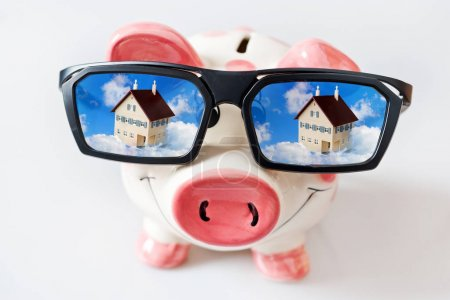 economy and finance - piggy bank with glasses and dreamed house - savings for a new house
