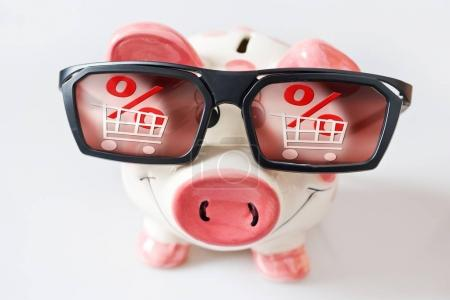 economy and finance - piggy bank with glasses and dreamed low prices in shops - savings for a shopping in sales
