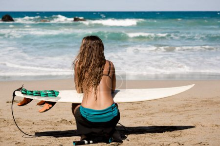 surfergirl is wating for the perfect wave with surfboard