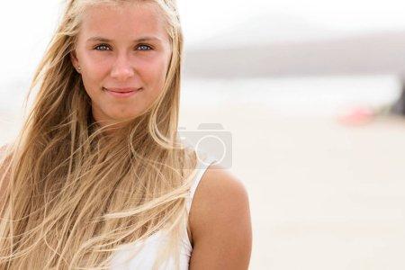 Photo pour Jeune femme aux yeux bleus et aux cheveux blonds à la plage - image libre de droit