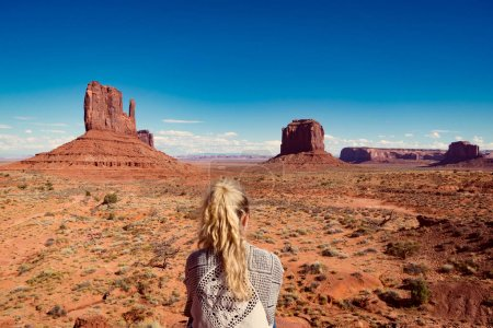 woman sitting in Monument Valley with red rocks overview