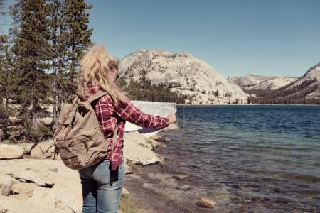 woman with map at a lake in Yosemite Park. wanderlust concept